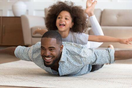 Gelukkige Afro-Amerikaanse vader liggend op vloertapijt met schattige dochter op de rug, die zich voordoet als vliegtuigen. Dolblij lachend meisje genieten van weekendtijd met papa, spelen, lachen. Actieve familie vrije tijd.