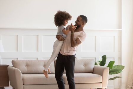 Happy african american daddy holding cute little daughter on hands, dancing together, having fun, celebrating Fathers day in modern living room at home, smiling family actively spending weekend time. Reklamní fotografie