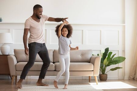 Excited loving african american smiling father twisting cute little kid daughter. Happy small girl dancing with daddy, having fun, enjoying spending weekend time together, morning family activities.