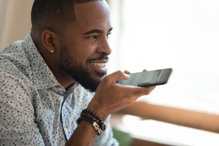 Close up happy smiling millennial african american man holding smartphone, dictating voice message, recording audio, using voice mic recognition mobile software, chatting with friends or family.