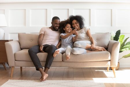 Smiling little mixed race girl holding smartphone, playing game, showing funny video to loving parents. Happy african american family sitting on comfortable couch in modern living room, using phone. Reklamní fotografie