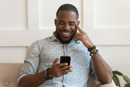 Happy smiling young african american guy holding cell phone, laughing at funny video or joke, chatting with friends or family in social networks, reading positive news, watching photos, web browsing.