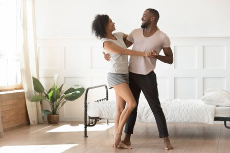 Happy african american man leading in passionate dance with smiling wife. Young married black family couple laughing, having fun in modern bedroom, weekend morning romantic activity, dating mood. Stockfoto