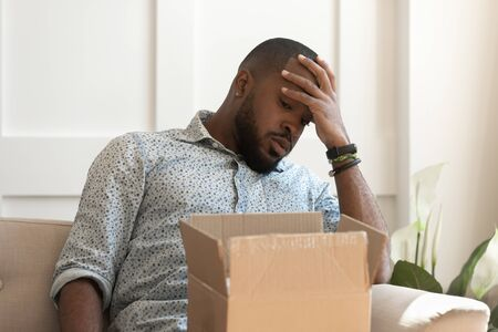 Dissatisfied unhappy african american male recipient sitting on couch, received parcel with wrong or damaged item, disappointed guy feeling upset with bad purchase in popular online store.