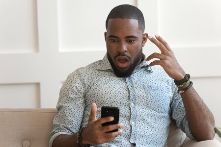 Surprised shocked millennial african american man holding phone, received mail with unbelievable news, amazing deal offer, grand sale discounts, new app free download, sitting on couch at living room.