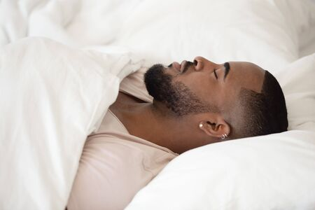 Close up young handsome black man lying on soft pillow in comfortable bed at home in bedroom or hotel, covered with blanket, sleeping, relaxing, having rest on vacation, lazy weekend concept. Reklamní fotografie