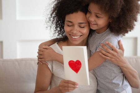 Excited happy african american loving sensitive mother embracing, bonding, hugging cute smiling adorable little mixed race daughter, holding handmade greeting card. Mothers Day celebration concept. Reklamní fotografie