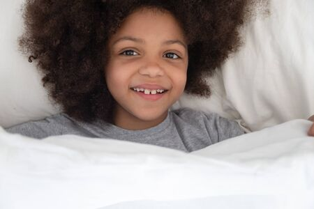 Top above view happy african american kid girl lying on pillow in bed under blanket, waking up in the morning after good dream, full of energy. Smiling mixed race adorable child looking at camera.