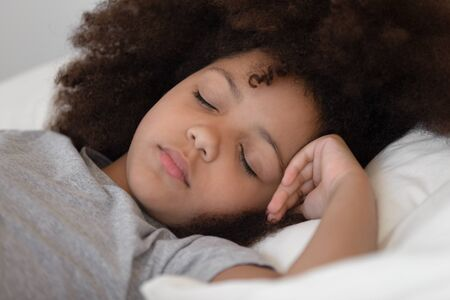 Close up cropped image mixed race cute peaceful child girl napping in bed. African american adorable preschool kid sleeping alone on soft pillow, resting at night or daydreaming in bedroom at home.