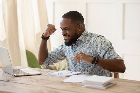 Euphoric young black man celebrating online lottery win, excellent educational online courses tests results, successful qualification training, getting remote dream work, received high paid job offer. Stock Photo - 129451414