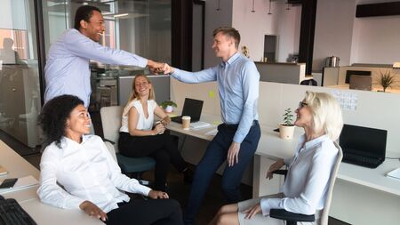 Excited diverse male employees give fist bump greeting at informal office meeting with colleagues, smiling man workers congratulate celebrating shared goal achievement or business success Stock Photo