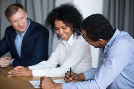 Glimlachende zwarte man onderhandelt met diverse zakenpartners ondertekenen samenwerkingsovereenkomst tijdens briefing, opgewonden multi-etnische zakenmensen sluiten deal zetten handtekening onder overeenkomst na succesvolle vergadering Stockfoto