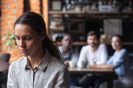 Verärgerte gemischtrassige Frau, die unter Mobbing, Diskriminierung leidet, ausgeschlossenes Mädchen, das Probleme mit schlechten Freunden hat, sich beleidigt und verletzt fühlt, allein im Café sitzt, Menschen meidet, soziale Ausgestoßene Standard-Bild