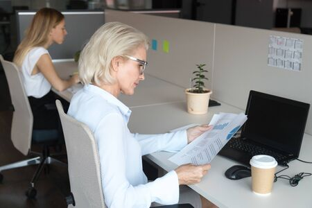 Concentrated middle-aged female employee sit at office desk checking paperwork financial statistics, focused senior woman read document report working on laptop in coworking office space