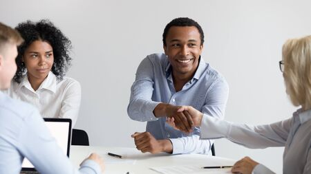 Smiling african American male employee shake hand greeting get acquainted with female colleague at office meeting, happy black businessman handshake woman business partner closing deal at briefing Stockfoto
