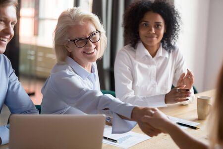 Sorridente imprenditrice di mezza età stringere la mano del collega introducendo seduti insieme alla riunione alla scrivania dell'ufficio, positivo senior dipendente femminile stretta di mano collega saluto fare conoscenza al briefing