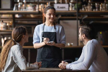 Pareja joven haciendo un pedido en la cafetería, atractiva camarera sonriente que sirve a los clientes, escribiendo en el bloc de notas, trabajadora de la cafetería hablando con el hombre y la mujer sobre el menú, ofreciendo comida y bebidas
