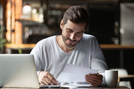Cheerful man doing paperwork in cafe, holding letter or legal document, sitting at table with laptop, checking post mail, customer drinking coffee, satisfied by receiving good news from bank