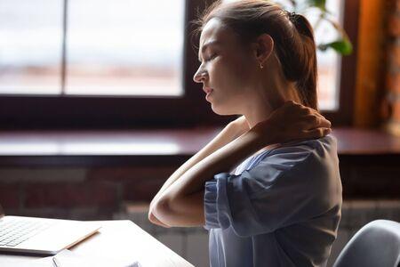 Müde Frau mit Nackenschmerzen nach sitzender Arbeit mit Computer in unbequemer Haltung oder Stuhl, erschöpfte Studentin oder Freiberuflerin massiert verspannte Nackenmuskulatur, Nahaufnahme Standard-Bild