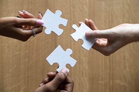 Close up of multiracial team employees hold jigsaw puzzle pieces involved in teambuilding activity assemble search right decision and best business solution, show unity and support. Teamwork concept
