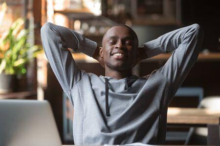 Hombre afroamericano satisfecho con los ojos cerrados relajándose después de terminar el trabajo con la computadora portátil en la cafetería, estudiante sonriente o autónomo recostado en una silla cómoda con las manos detrás de la cabeza