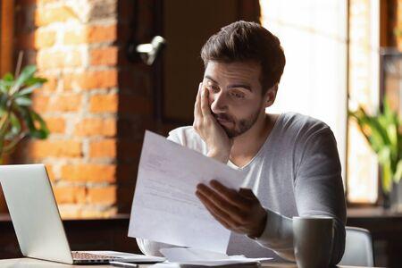 Verwirrt frustrierter junger Mann, der Brief im Café liest, Schuldenbenachrichtigung, schlechter Finanzbericht, Geldproblem, Geldproblem, verärgerter Schüler, der schlechte Nachrichten erhält, erfolglose Prüfungs- oder Testergebnisse