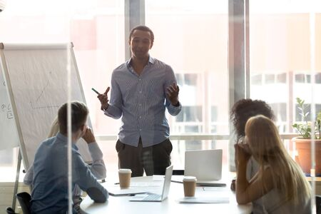 African American male speaker make flip chart presentation in boardroom for diverse employees, black businessman present project on whiteboard talk coach workers at company office training
