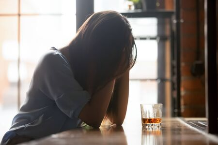 Lonely unhappy woman sitting alone with glass of whiskey, hiding face in hands, thinking about problem at work or relationship problems, feeling desperate and depressed, alcohol addiction concept