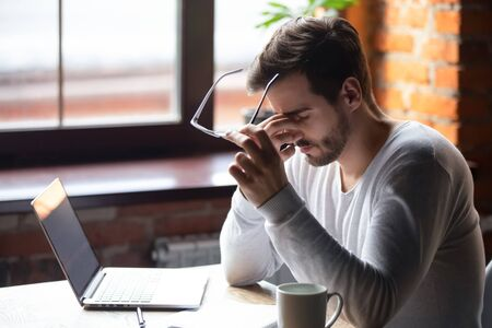 Upset man massaging nose bridge, taking off glasses, feeling eye strain after long work with laptop, sitting in cafe, tired male feeling discomfort after long wearing glasses, bad eye vision concept Stock fotó