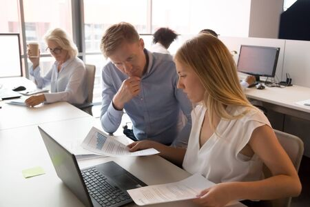 Concentrated diverse employees talk discuss financial report analyzing sales working together in shared office, man and woman worker negotiate checking reading paperwork statistics. Teamwork concept