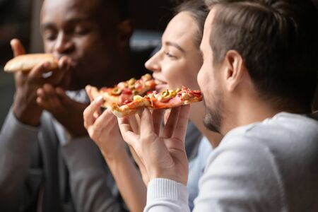 Close up happy diverse friends eating pizza in cafe together, biting slices, multiracial people enjoying Italian junk food at meeting in cafeteria, having fun together, satisfied customers