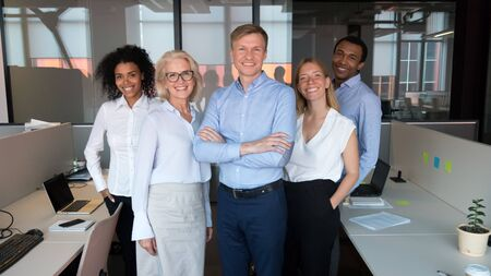 Smiling multiethnic team with Caucasian male leader forefront look at camera posing for group picture at workplace, motivated diverse colleagues make photo together showing unity and support