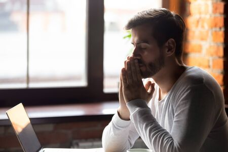 Worried man thinking about problem solution, pondering important question, puts hands together in prayer, upset sitting alone with closed eyes, frustrated about difficulties, taking break, breathing