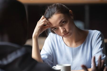 Bored unhappy girlfriend listening to African American boyfriend in cafe, bad first impression and date concept, multiracial couple having sitting at table, talking, having problem in relationships Stock Photo