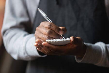 Chiudere le mani del cameriere afroamericano con il taccuino, prendere l'ordine del cliente al bar o al ristorante, lavoratore della caffetteria che indossa un grembiule nero che serve il cliente, scrivere, concetto di servizio