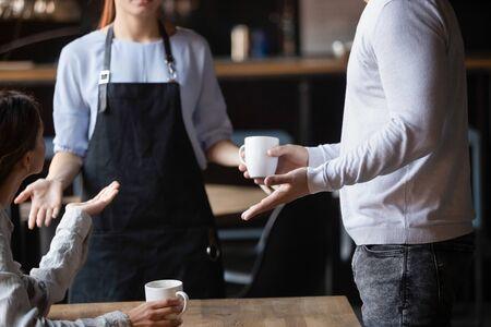 Cerrar clientes indignados discutiendo con la camarera en la cafetería, mal concepto de servicio, hombre y mujer enojados infelices disgustados por la mala calidad de las bebidas, hablando, en conflicto con el trabajador del café