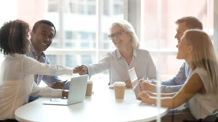 Middle-aged businesswoman handshake with african American female business partner greeting at meeting, diverse employees shake hands get acquainted introduce at company team briefing