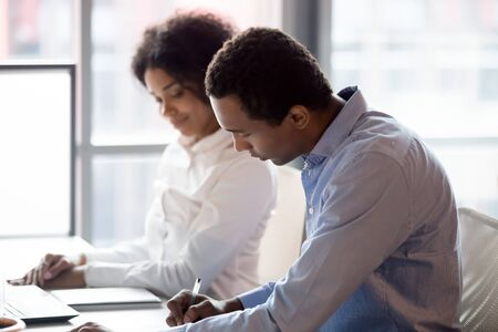 Focused african American boss at workplace write evaluate female trainee internship at company, black millennial female intern or employee look at male supervisor assess her work results or report