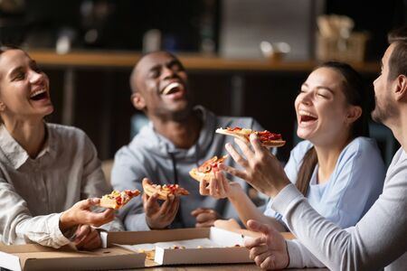 Diverse friends eating pizza, happy colleagues or students having fun together in cafe, men and women laughing at funny joke, holding Italian junk food slices in hands at meeting in cafeteria Stock Photo