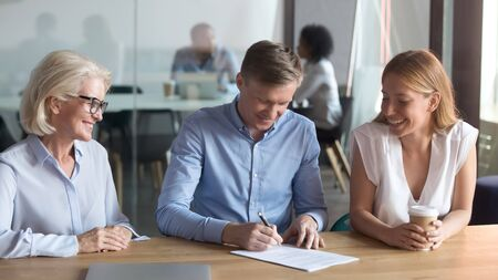 Happy husband put signature on contract buy first house from realtor together with excited young wife, overjoyed couple tae loan sign agreement after successful meeting with female banker or realtor Stock fotó