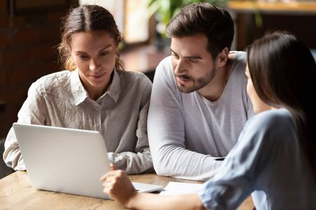 Realtor or insurance broker consulting young couple in cafe, sitting together at table, using laptop, looking at screen, financial advisor discussing mortgage or loan conditions with clients 스톡 콘텐츠