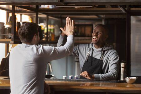 Sorridente barista afroamericano che dà il cinque con il cliente, barista eccitato che indossa un grembiule in piedi dietro il bancone del bar, saluta un amico o un cliente abituale nel caffè, celebra il successo