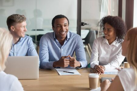 Smiling multiethnic colleagues brainstorm at office desk discussing financial statistics at meeting, positive diverse businesspeople negotiate share thoughts cooperating at briefing in boardroom Banque d'images