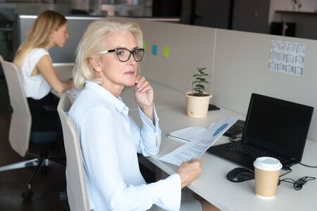 Thoughtful middle-aged female employee sit at office desk look in distance distracted from office work, pensive senior woman hold paperwork thinking or dreaming take pause from job in coworking space