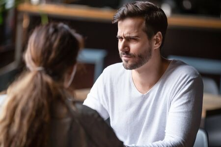 Doubting dissatisfied man looking at woman, bad first date concept, young couple sitting at table in cafe, talking, bad first impression, new acquaintance in public place, unpleasant conversation Stock Photo