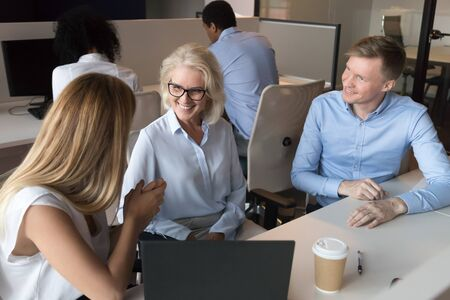 Happy diverse employees sit at office desk in shared workplace talking discussing ideas, smiling colleagues chat sharing thoughts brainstorming together in coworking space. Cooperation concept Imagens