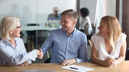 Smiling middle-aged female realtor handshake excited husband closing deal with overjoyed first time buyers couple, happy spouse shake hand signing agreement with banker take property loan or mortgage