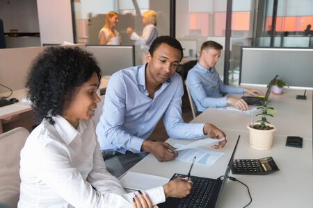 African American male supervisor test black millennial female intern check skills at laptop at workplace, company team leader brainstorm work together with colleague on computer in coworking office Imagens