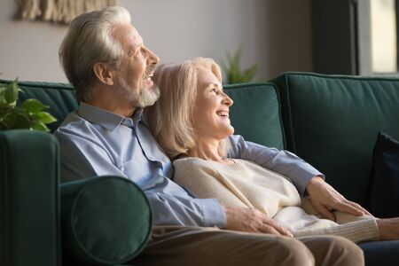 Happy smiling older family couple embracing, dreaming, looking outside, planning future life, lying, relaxing on the couch at home. Gray-haired elderly healthy couple enjoying retirement lifestyle.