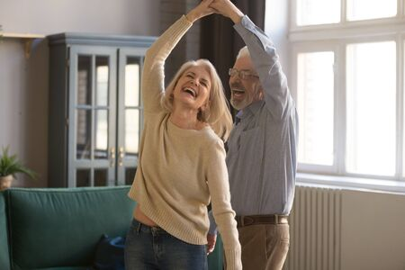 Overjoyed mature grey-haired Caucasian husband and wife have fun enjoy time together at home, happy elderly couple spouses dancing in living room, senior man lead sway smiling middle-aged woman Imagens